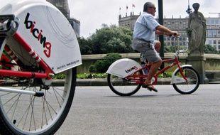 Un homme fait du vélo en libre-service à Barcelone, le 18 juin 2007