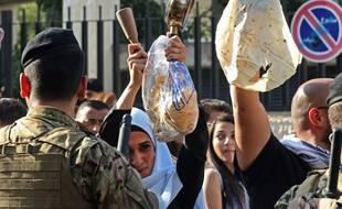 Une manifestante libanaise munie d'une casseroles devant une succursale de la banque centrale lors des manifestations antigouvernementales en cours à Sidon (Saïda), une ville du sud du Liban, le 8 novembre 2019.