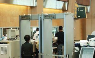 Des voyageurs passant aux détecteur de métaux d'un aéroport. Illustration.