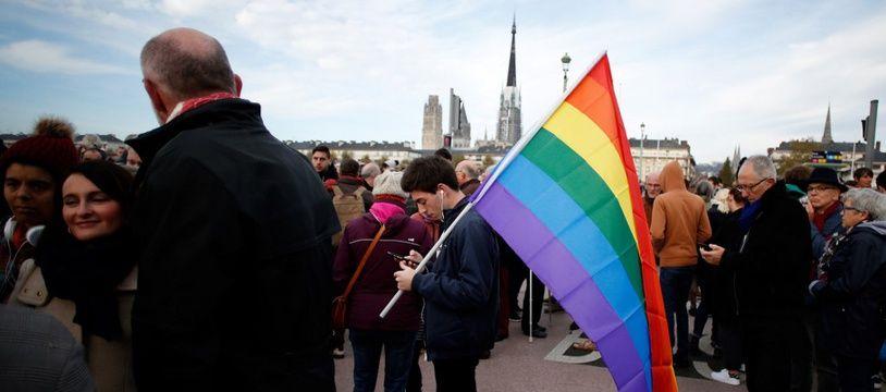 Un homme tient un drapeau arc-en-ciel, emblème de la communauté LGBT, lors d'une manifestation contre l'homophobie. (illustration)
