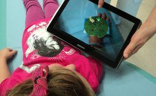 Grâce à la réalité augmentée, le personnage virtuel dédramatise l'acte médical et rassure l'enfant.