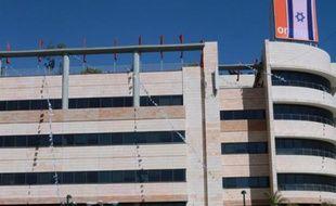 Un drapeau israélien recouvre le logo d'Orange, sur un bâtiment du groupe de télécoms israélien Partner, à Rosh Haain, près de Tel Aviv, le 11 juin 2015
