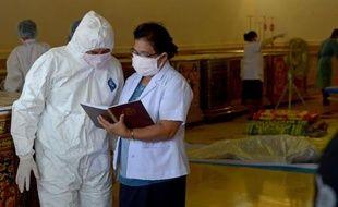 Des médecins légistes thaïs et laotiens établissent la liste des victimes d'un accident d'avion, le 19 octobre 2013 à Paksé, au Laos