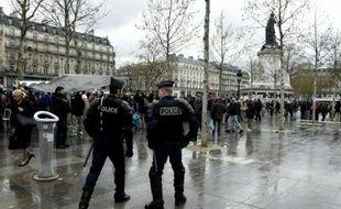 """Des policiers regardent quelques centaines de personnes se rassemblaient place de la République pour une assemblée générale du mouvement """"Nuit debout"""", à Paris le 11 avril 2016"""