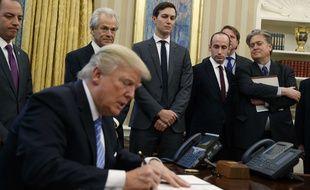 Donald Trump entouré de ses conseillers Stephen Miller et Steve Bannon (tout à droite), Jared Kushner (centre) et de son chef de cabinet, Reince Priebus (gauche.
