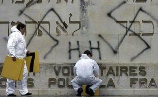 Des gendarmes effectuent des relevés après que des tags néonazis et des croix gammées ont été tracés sur le monument à la mémoire des combattants israélites tués pendant la bataille de Verdun durant la Première guerre mondiale, le 07 mai 2004 à Fleury-devant-Douaumont