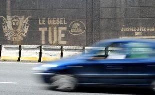 """Une voiture passe devant un graffiti """"le diesel tue"""" sur les berges de Seine à Paris"""