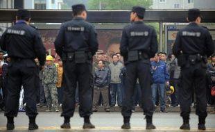 Des policiers chinois à l'extérieurs d'un tribunal à Xianning le 31 août 2014 durant un procès anticorruption