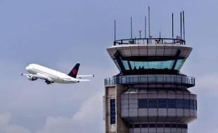 Un avion décolle devant une tour de contrôle