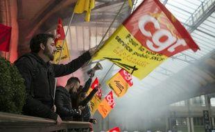 Un manifestant agitant un drapeau de la CGT lors d'une grève à la SNCF, le 26 avril 2016 à la Gare de Lyon à Paris.