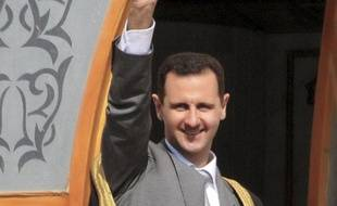Le président syrien Bachar al-Assad salue la foule lors d'une visite dans al ville d'Ar-Raqqa, en Syrie, le 6 novembre 2011.
