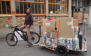 Adrien en pleine démonstration de déménagement à vélo, avec son plateau qui peut transporter jusqu'à 300 kilos de bagages.
