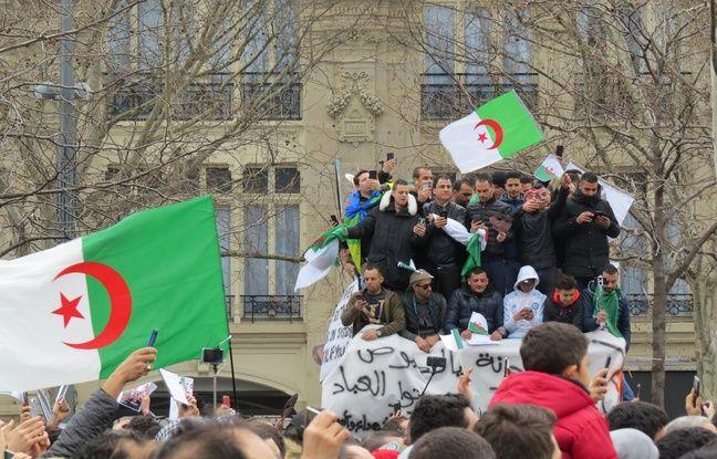 Sur un abribus, des manifestants chantent et montrent leur drapeau lors de cette manifestation place de la République dimanche 3 mars 2019.