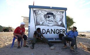 Des insurgés libyens se tiennent devant une caricature de Mouammar Kadhafi, le 14 juin 2011, près de Misrata (Libye).