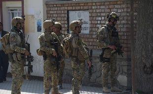 Les militaires afghans patrouillent devant l'université de Kaboul après l'attentat suicide qui a fait 26 morts, le 21 mars 2018.