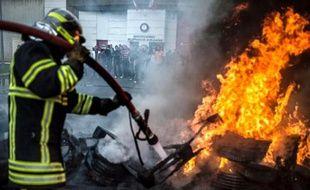 Un pompier éteint un début d'incendie devant la prison de Villefranche-sur-Saône après une manifestation de gardiens de prison le 6 mai 2014 contre la surpopulation carcérale et le manque de moyens sanitaire pour les détenus
