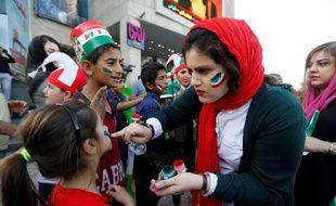 Une supportrice iranienne maquille une jeune fille avant le match contre le Maroc à Kazan.