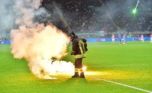 Un pompier ramasse des fumigènes sur la pelouse de San Siro lors d'un match entre l'Italie et la Croatie, le 16 novembre 2014 à Milan.