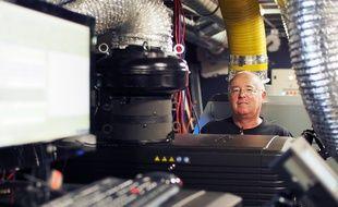 Eric Falcon prend la pose entre un projecteur numérique et un argentique