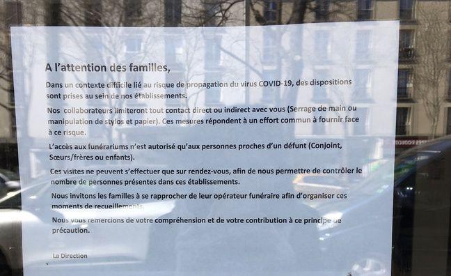 Une société de pompes funèbres a affiché les restrictions liées à l'épidémie de coronavirus, à Paris en face du cimetière du Père-Lachaise.