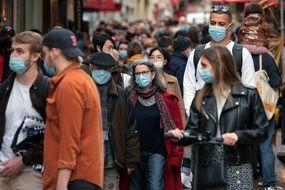 Une foule masquée dans une rue parisienne. (illustration)