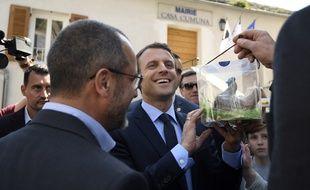 Emmanuel Macron content de recevoir un cadeau, un coq en chocolat, lors de sa visite à Vescovato en Corse le 7 avril 2017.