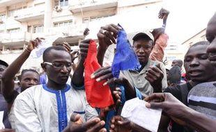 Des manifestants sénégalais brûlent un drapeau français, le 16 janvier 2015 à Dakar, pour protester contre la publication d'une caricature de Mahomet par Charlie Hebdo
