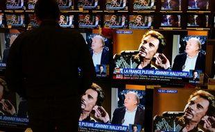 Le 6 décembre 2017, dans un magasin à Lille, un homme fait face à des téléviseurs diffusant des informations sur la mort de Johnny Hallyday.
