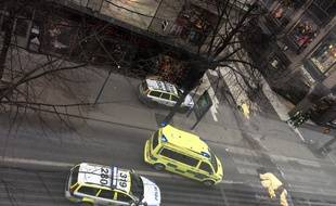 An ambulance standsa near covered bodies at the scene where a truck crashed into the Ahlens department store at Drottninggatan in central Stockholm, April 7, 2017.