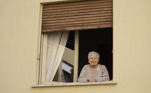 Une personne âgée regardant à la fenêtre lors du confinement, illustration