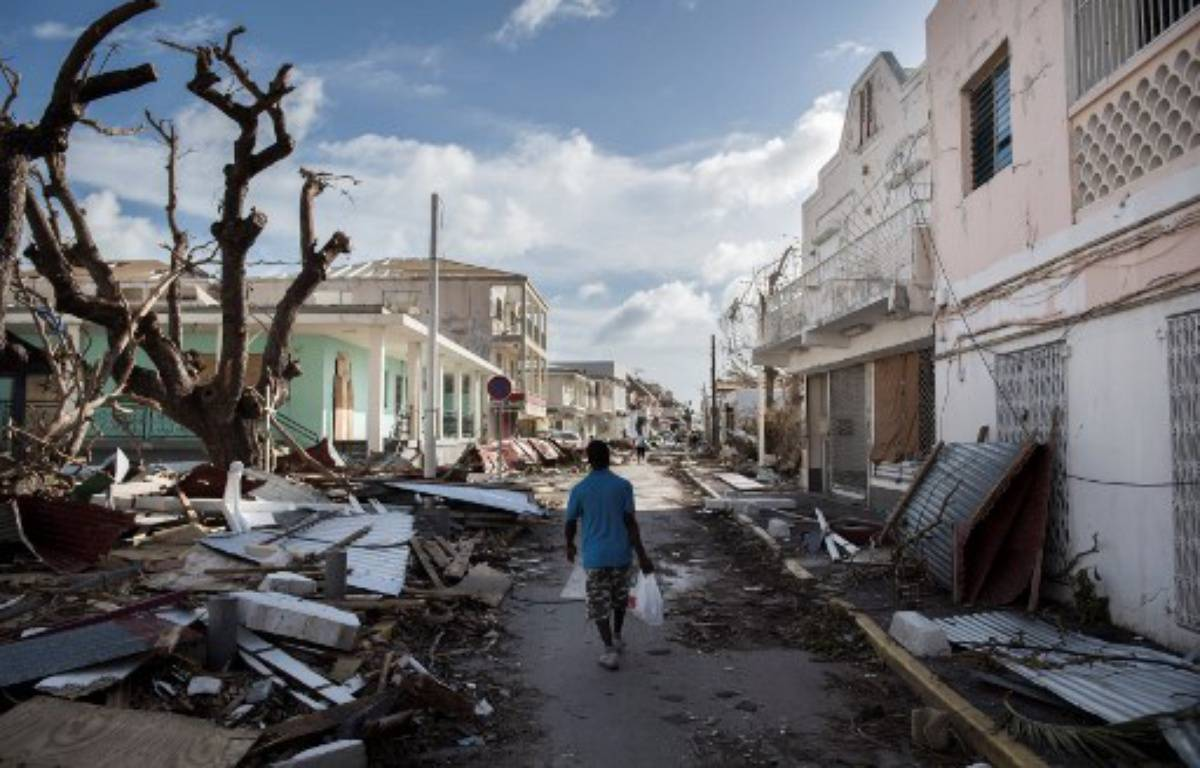 Un homme marche dans une rue couverte de débris après le passage de l'ouragan Irma à Saint-Martin,  le 8 septembre 2017. – Martin BUREAU / AFP