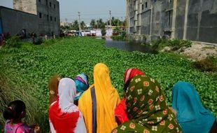 Des femmes bangladaises regardent le 24 avril 2016 le site où s'est effondré le bâtiment du Rana Plaza il y a trois ans, dans lequel plus de 1.100 personnes avaient trouvé la mort, près de Dhaka