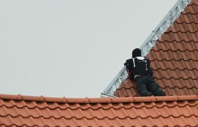 Un membre des Forces spéciales Belges prend position sur un toit, lors de l'opération à Forest, le 15 mars 2016