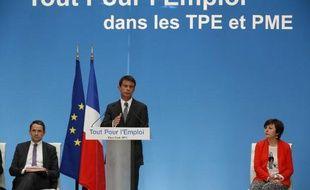Le Premier ministre Manuel Valls (c) et les secrétaires d'Etat à la Réforme de l'Etat Thierry Mandon (g) et chargée du Commerce, de l'Artisanat, de la Consommation et de l'Économie sociale et solidaire Carole Delga à Paris, le 9 juin 2015