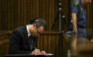 Oscar Pistorius prend des notes lors de son procès, à Pretoria le 11 mars 2014