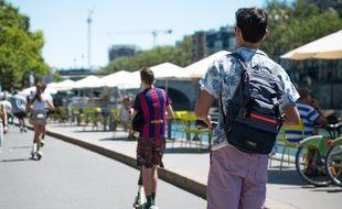 Deux jeunes hommes à trottinette sur les quais de Seine, à Paris Plages, le 9 juillet 2019.