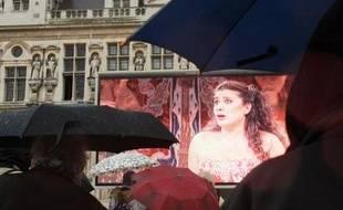 Pas découragées par la pluie, des fans d'opéra regardent, le 24 mars 2008 sur un écran géant disposé sur la façade de l'Hôtel de ville à Paris, un concert triomphal que la mezzo italienne Cecilia Bartoli a donné en novembre 2007 à Barcelone.