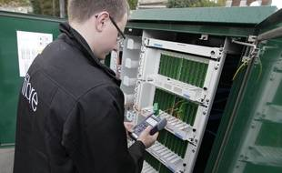 Un technicien installe de la fibre optique à une armoire de raccordement.