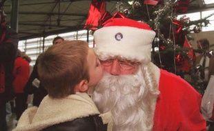 Photo d'illustration montrant un enfant en train d'embrasser un père Noël.