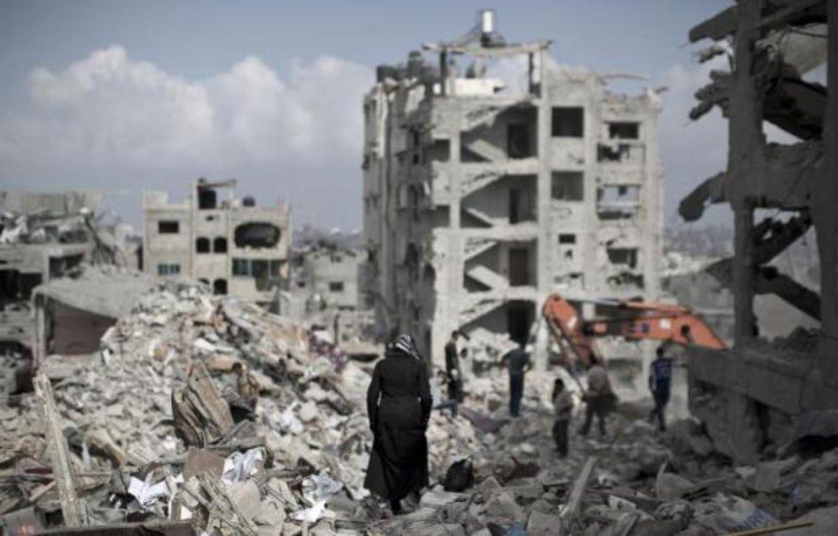 Une femme palestinienne marche au milieu de ruines près de Gaza City, le 6 août 2014 – Mahmud Hams AFP