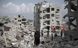 Une femme palestinienne marche au milieu de ruines près de Gaza City, le 6 août 2014
