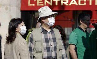 Des touristes asiatiques portent un masque, pour se protéger du virus de la grippe A (H1N1) dans le centre de Paris, mai 2009.