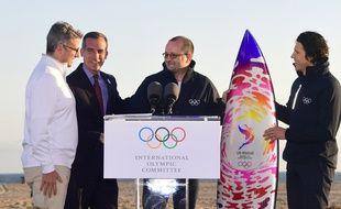 Le maire de Los Angeles, Eric Garcetti  et Casey Wasserman, le président de LA2024 (à gauche) ont offert une planche de surf à Patrick Baumann (au centre) et Christophe Dubi (à droite) du Comité international olympique lors de leur visite en Californie le 11 mai 2017.