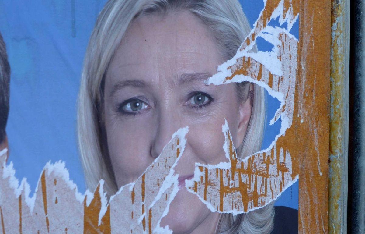 Affiche déchirée de Marine Le Pen, candidate en Nord-Pas-de-Calais-Picardie aux élections régionales. – ALLILI MOURAD/SIPA