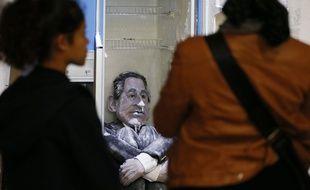 Des visiteurs du Palais de Tokyo regardent l'installation mettant en scène la marionnette de Nicolas Sarkozy, lors de l'édition 2012 de la Nuit blanche, à Paris.