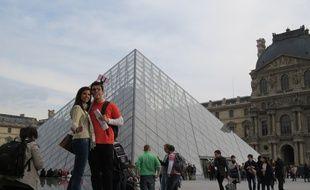 Deux touristes se prenant en portrait devant la pyramide du Louvre aidés d'une perche à selfie.