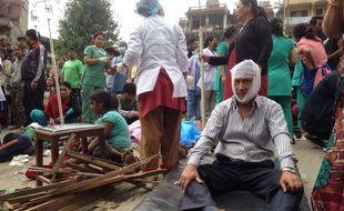Des blessés reçoivent des soins devant l'hôpital Medicare à Katmandou, après le séisme qui a touché le Népal le 25 avril 2015.