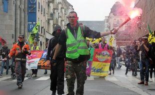 Un manifestant brandit un fumigène lors d'un défilé contre la loi Travail, ici le 14 juin à Rennes.