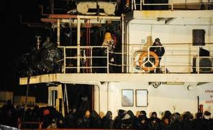 Des refugiés syriens attendent de débarquer au port italien de Gallipoli, le 31 décembre 2014. Leur bateau, le Blue Sky M, a été secouru par les gardes-côtes italiens, après avoir été abandonné avec quelque 800 personnes à bord par les passeurs
