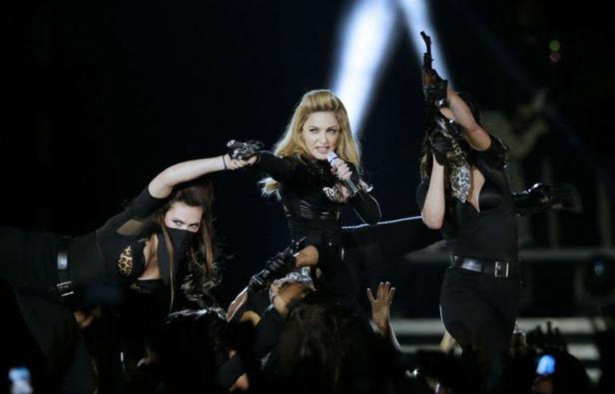 """Marine Le Pen va porter plainte pour """"injure"""" contre la pop-star américaine Madonna qui a de nouveau projeté samedi soir lors d'un concert au Stade de France un clip vidéo dans lequel apparaît brièvement la présidente du FN, affublée d'une croix gammée sur le front. – Kenzo Tribouillard afp.com"""